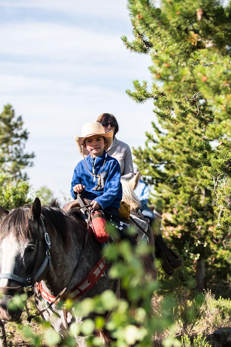 Small boy comfortably riding horse