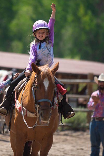 Little girl triumphantly riding horse
