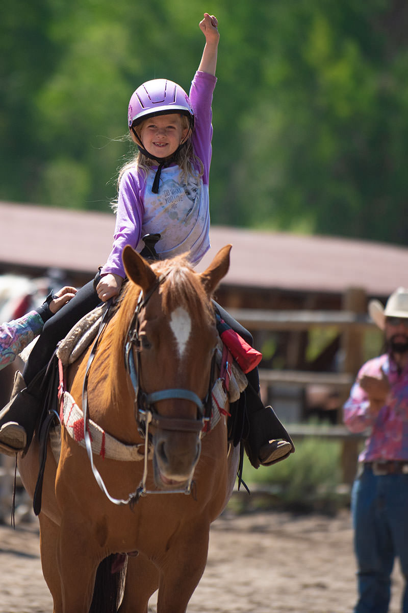 Little girl triumphantly riding horse