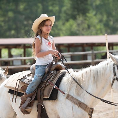 Little cowgirl comfortably sitting on white horse
