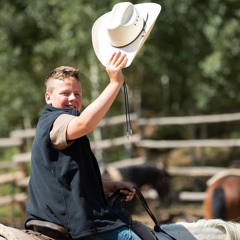Boy waving hat and smiling on horseback