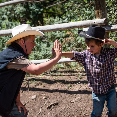 Young child getting a high five from older boy