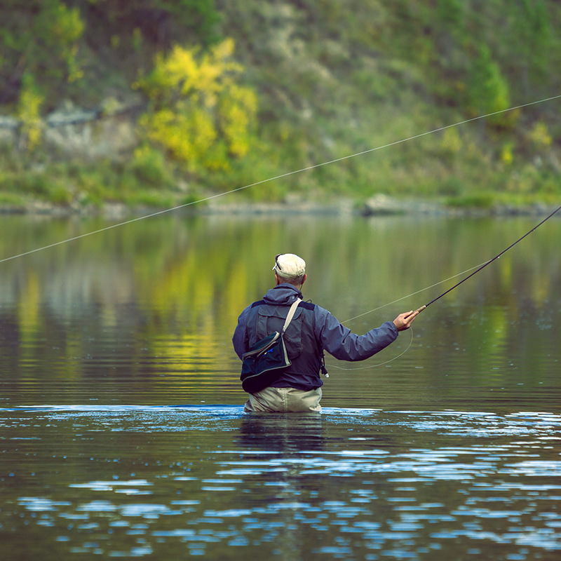 Fly fisherman wading in the deep river